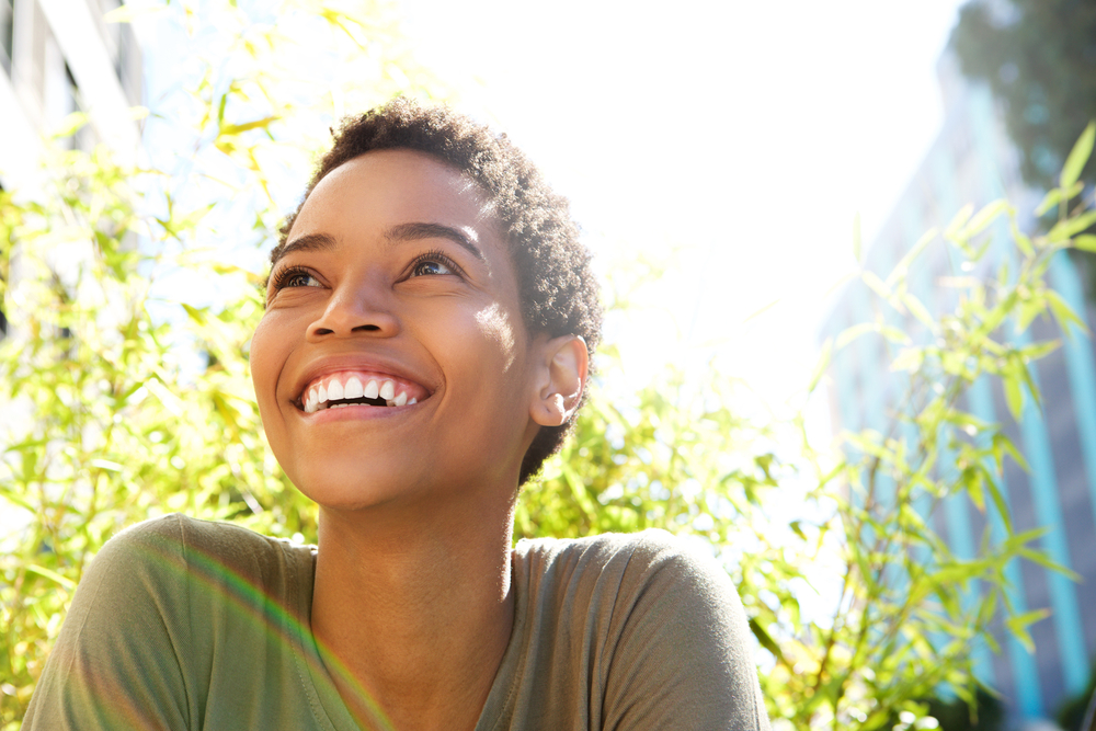 young woman smiling outdoors on a sunny day